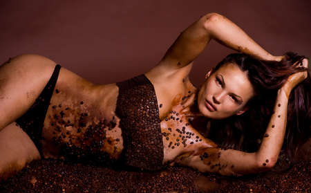 Sexy young woman in coffee beans with beautiful brown make-up Stock Photo - 14372539