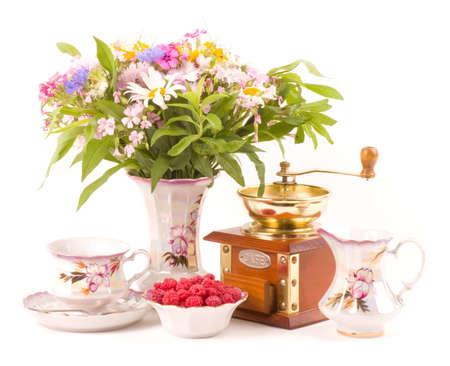 Vintage elegant teacups, raspberry, coffee grinder and flowers photo