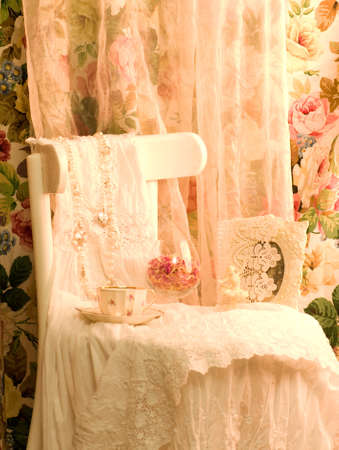 Vintage white dress, teacup and frame on white chair photo