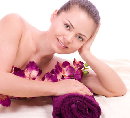 Beauty spa woman with towel and pink orchid on background