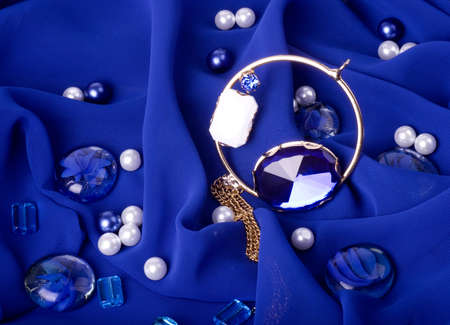 Golden jewelry on blue background photo