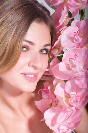Beauty face of the young woman with pink orchid on background photo