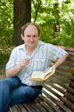 Mature pretty man reading book, outdoor  photo