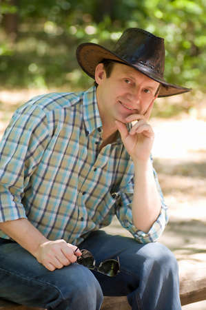 Pretty man with cowboy hat  in the forest photo