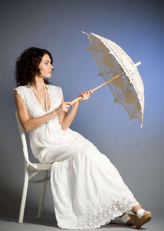 Young woman in retro bridal dress with umbrella photo