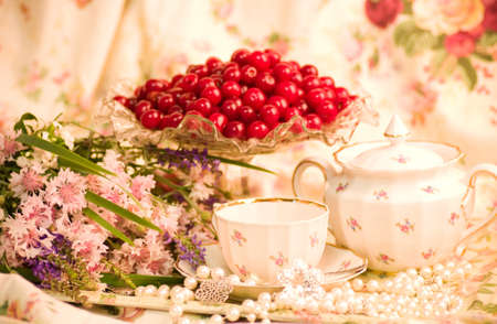 Vintage tea in elegant tableware, raspberry, cherry and flowers photo
