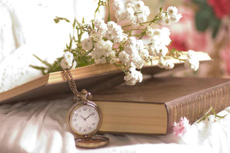 White flowers, book and clock photo