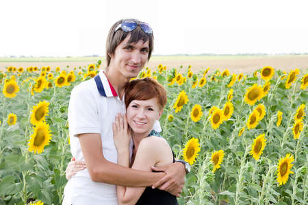 Loving couple in a field of sunflowers photo