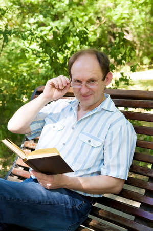 Happy aged man with glasses reading book in park photo