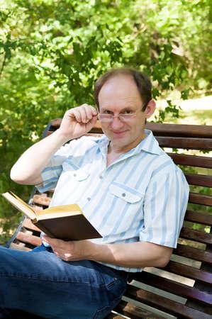 Heureux homme âgé avec des lunettes de lecture livre dans le parc Banque d'images - 14875004