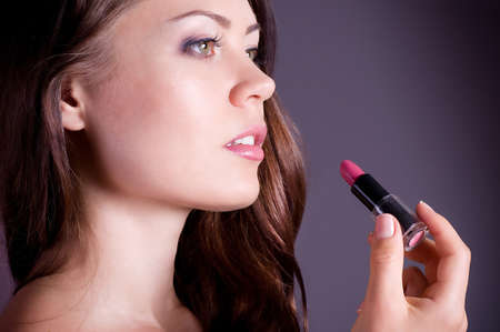 woman applying pink lipstick  Professional Make-up photo