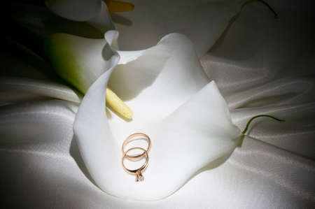 Beautiful white callas with wedding golden rings photo