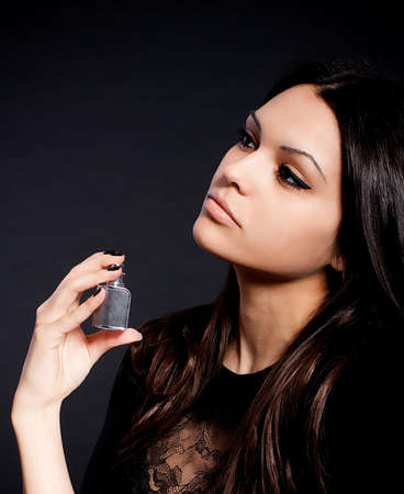 Portrait of beautiful young woman with perfume bottle photo