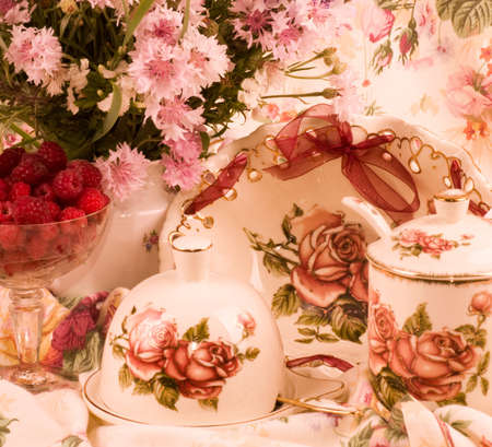 Vintage tea in elegant tableware, raspberry and flowers photo