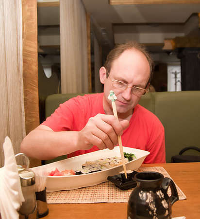 Aged man eating sushi rolls in cafe photo