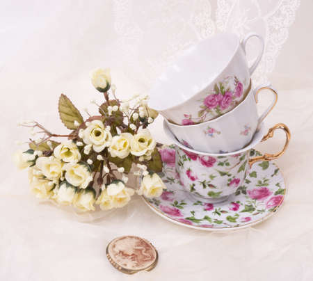 Vintage elegant cups with cameo and flowers photo