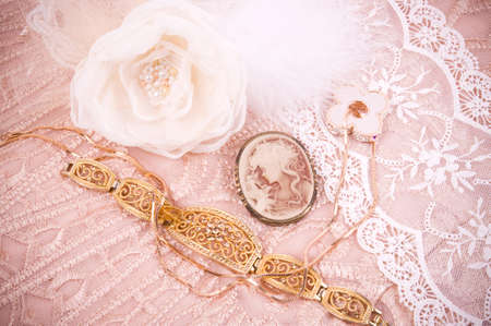 White lace with flower, golden jewelry and antique cameo 스톡 콘텐츠