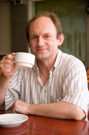 Happy aged man with coffee in cafe photo