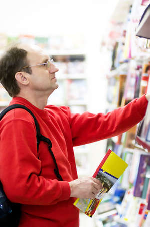 Mature man reading a book with glasses in bookshop photo