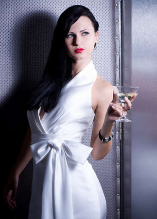 Vintage woman in retro dress with martini on dark background photo