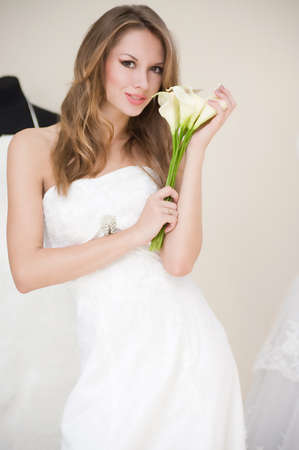 Beautiful bride with stylish make-up in white dress photo