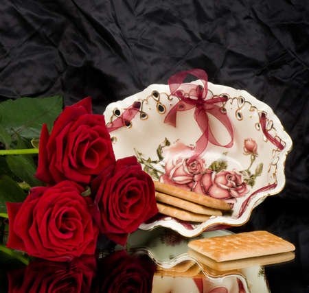 Beautiful porcelain plate with cupcakes and red roses photo