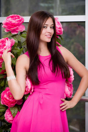 Beautiful young woman in fashion pink clothes photo