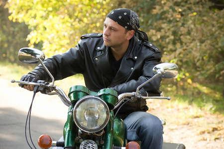 motociclista: Biker hombre se sienta en una bicicleta en el parque Foto de archivo
