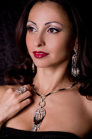 Portrait of beautiful young woman with jewelry on black background photo
