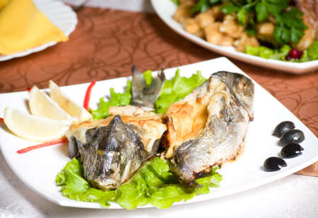 Fried fish garnished on sliced olive and sauce photo