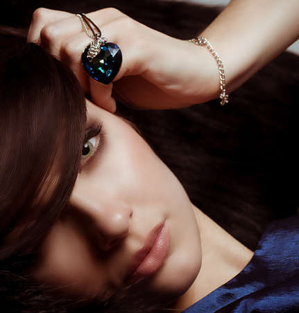 jewlery: Portrait of beautiful young woman with makeup in luxury jewelry