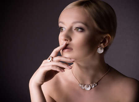 jewel hands: Portrait of beautiful young woman with makeup in luxury jewelry