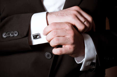 Closeup of a man in black suit correcting a sleeve photo