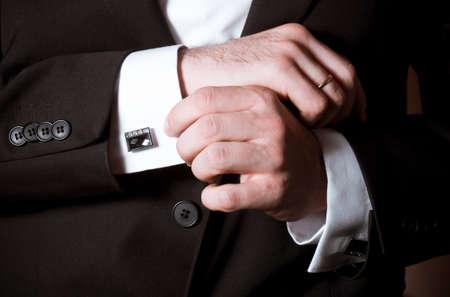 Gros plan d'un homme en costume noir corriger un manchon Banque d'images