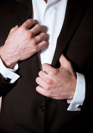 cufflink: Closeup of a man in black suit with cuff-link Stock Photo