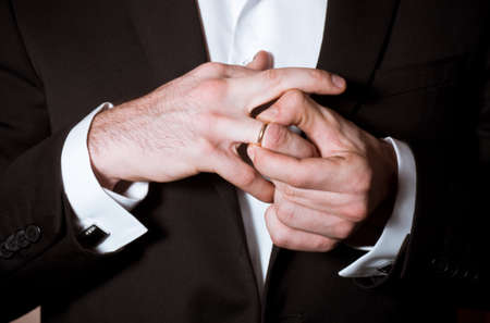 Close-up of elegance groom hands takes off a ring Stock Photo - 17133060