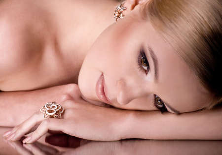 jewellery design: Portrait of beautiful young woman with makeup in luxury jewelry