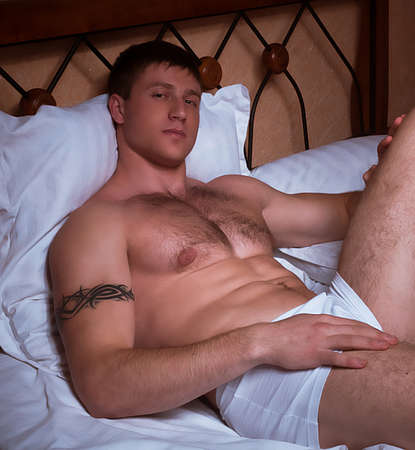 only 1 man: Young sexy muscular man in a bed