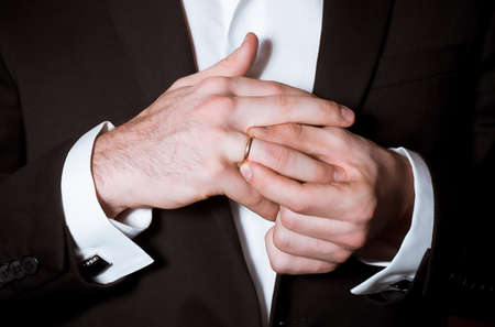 Close-up of elegance groom hands takes off a ring Stock Photo - 17804436