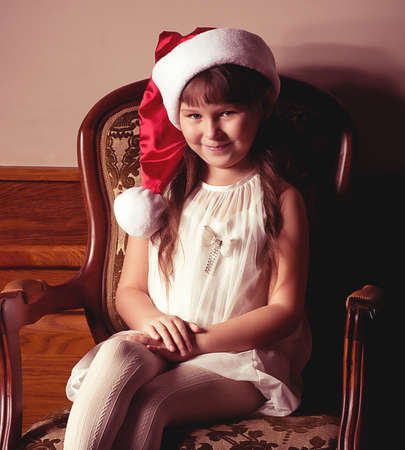 Beautiful little girl in Santa Claus clothes photo