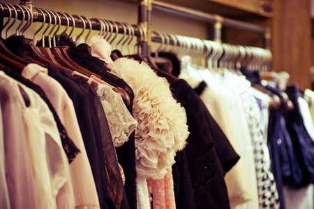 tienda de ropas: La elecci�n de la ropa de moda de diferentes colores en perchas de madera