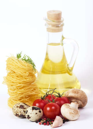 Italian pasta with vegetables, quail eggs, olive oil and spices on white background photo
