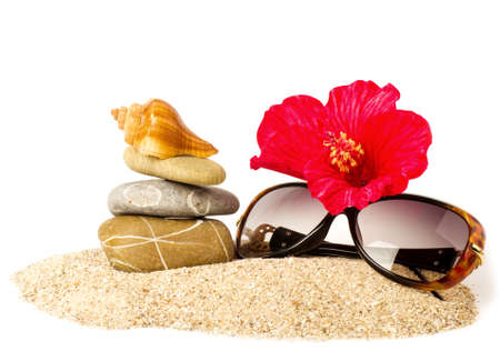 Beautiful exotic shell, stones, red flower and glasses on sand photo