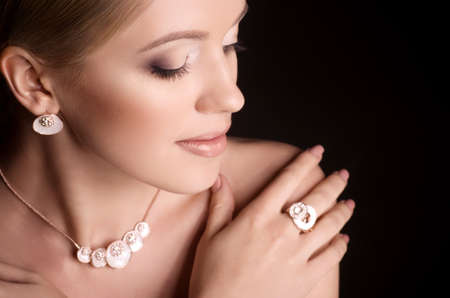 Portrait of beautiful young woman with makeup in luxury jewelry photo
