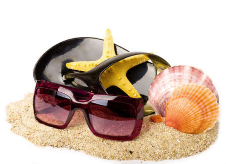 Beautiful exotic shell, shoe and glasses on sand photo