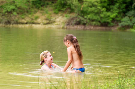 Little girl and her mother have a good time in lake photo