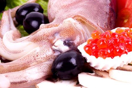 dedo me�ique: Calamares con verduras y caviar rojo sobre el fondo blanco Foto de archivo