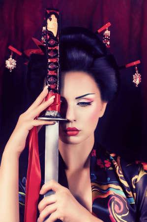 katana: Mooie geisha in kimono met samurai zwaard Stockfoto
