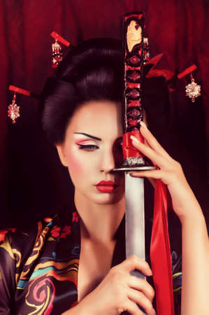 traditional weapon: Beautiful geisha in kimono with samurai sword