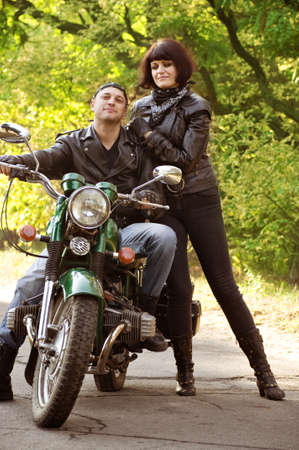 Couple of lovers sitting by motorcycle photo